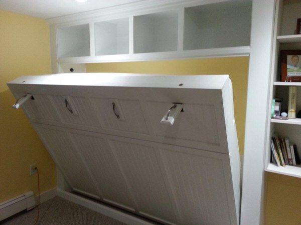 Custom built-in pull down queen size Murphy bed for a basement office. Unit was designed to fit in a tight space between an existing bookcase and corner. The unit was built as several components and assembled and installed on site so that we could get it down the tight staircases.
